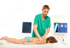 Masseur doing deep tissue back massage to child Stock Photo