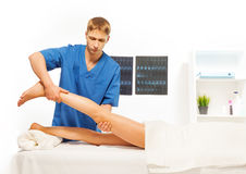 Masseur doing exercises with woman leg Stock Image
