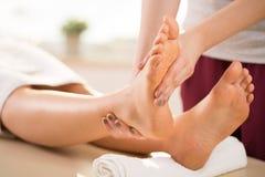 Masseur doing leg massage Stock Photography