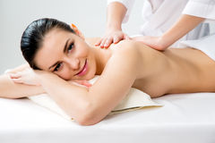Masseur doing massage on the back of woman in the spa salon. Stock Photography