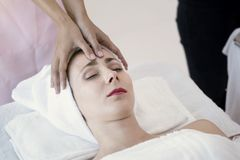 Masseur doing massage the head of beautiful young woman relaxing Stock Image