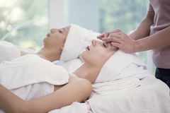 Masseur doing massage the head of beautiful young woman relaxing Royalty Free Stock Images