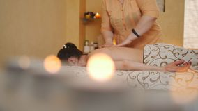 Professional female masseur doing back massage for woman client at spa salon, studio. Wellness, relaxation and