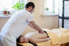 Masseur doing massage on woman's back Royalty Free Stock Photography