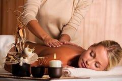 Masseur doing  massaging  back of beautiful woman Stock Photo