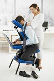 Masseur doing neck massage in office royalty free stock image