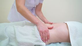 Masseur féminin employant l'huile d'arome pour masser l'abdomen de femme clips vidéos