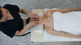 Masseur f?minin professionnel faisant le massage pour le jeune client banque de vidéos