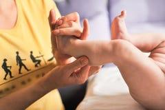 Masseur faisant le massage pour le petit bébé de pied Image stock