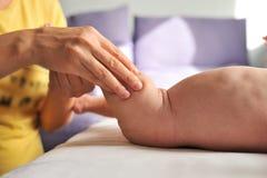 Masseur faisant le massage pour le petit bébé de pied Photographie stock libre de droits