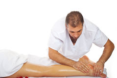 Masseur give therapeutic massage to woman legs royalty free stock images