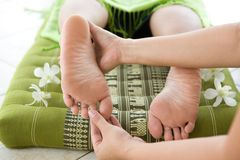 Masseur giving female patient a foot reflexology. Royalty Free Stock Photos