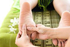 Masseur giving female patient a reflexology. Royalty Free Stock Photo