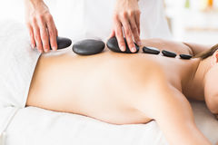 Masseur giving hot stone massage to woman Royalty Free Stock Image