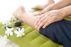 Masseur giving lady patient a leg massage Royalty Free Stock Image