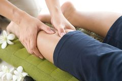 Masseur giving lady patient a leg massage . Royalty Free Stock Photos