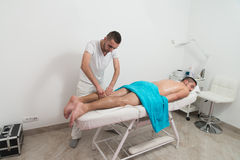 Masseur Giving Legs Massage To A Man Stock Photography