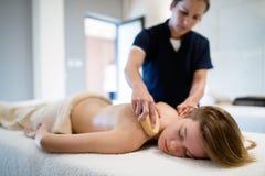 Masseur massaging masseuse at wellness resort. Masseur giving massage therapy to masseuse at wellness resort stock image
