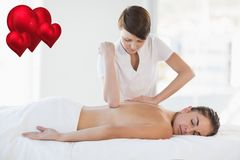 Masseur giving massage to woman at spa. Composite image of masseur giving massage to woman at spa Royalty Free Stock Photo