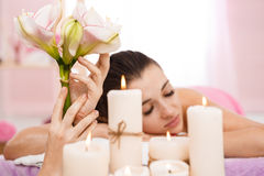 Masseur hands holding beautiful flowers behind candles. Relaxation and comfort Stock Photos