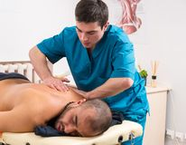 Masseur kneading the back muscles of a client. Masseur kneading the back muscles of a male client to stimulate and relax them as he lies on a couch in a spa or royalty free stock image