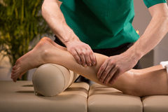Masseur kneading female calf Royalty Free Stock Image