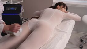 Masseur makes apparatus anti-cellulite massage in the cosmetology clinic