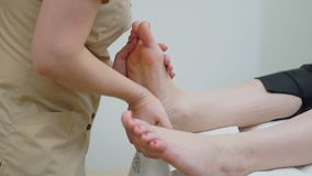 The masseur makes a therapeutic foot massage to the girl. Close-up.