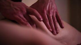 The masseur massages the girls leg buttock with hands under romantic low light