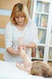 Masseur massaging a child leg Stock Photos
