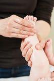 Masseur massaging a child leg Royalty Free Stock Photography