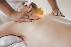 Masseur massaging customer's back in spa salon at luxury resort or hotel. Beautiful customer woman feel relaxing, comfortable. royalty free stock photography