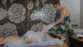 The masseur massaging with foam the left foot in the Turkish bath. Cute girl laying the head on the hands on the table in the Turkish bath with foam on the back stock footage