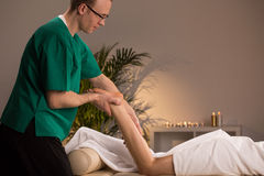 Masseur massaging lower limb Royalty Free Stock Photos