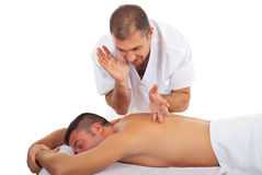 Masseur massaging man back Stock Images