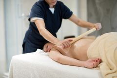 Masseur massaging masseuse at wellness resort. Masseur giving massage therapy to masseuse at wellness resort stock images
