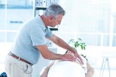 Masseur massaging pregnant woman Royalty Free Stock Image