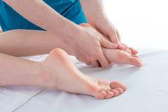 Masseur massaging woman foot royalty free stock image