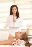 Masseur meditating over patient. Before starting massage stock image