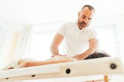 Masseur man doing massage manipulations on the client back and communicate with patient. Masseur men doing massage manipulations on the client back and royalty free stock photo