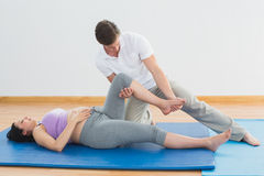 Masseur moving pregnant womans leg on blue mat Royalty Free Stock Images