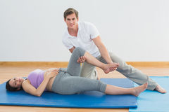 Masseur moving pregnant womans leg on blue mat smiling at camera Royalty Free Stock Images