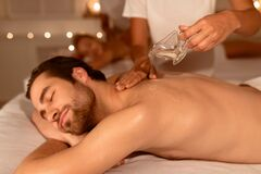 Masseur Pouring Oil During Couples Massage Therapy At Spa