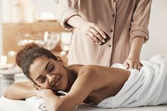 Masseur pouring oil doing massage for beautiful african girl in spa salon. Masseur pouring oil doing massage for young beautiful african girl in spa salon Stock Images