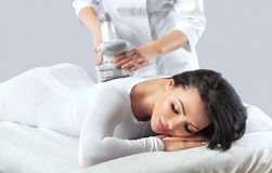 The masseur is preparing to make an hardware anti-cellulite massage. In a beauty salon royalty free stock images