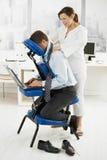 Masseur que faz a massagem da garganta no escritório imagem de stock royalty free