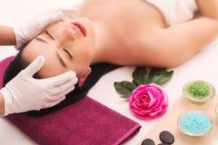 Masseur som gör massage på kvinnahuvuddel i brunnsortsalongen Stående över vit bakgrund fotografering för bildbyråer
