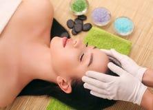 Masseur som gör massage på kvinnahuvuddel i brunnsortsalongen Stående över vit bakgrund arkivbild