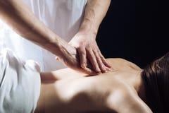 Masseur som g?r massage p? kvinnahuvuddel i brunnsortsalongen Kvinna i brunnsortsalongen, massage St?ende ?ver vit bakgrund Flick royaltyfri foto