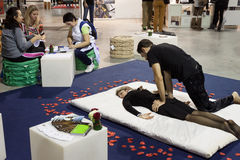 Masseur with young woman at Weekend Donna 2013 in Milan, Italy Stock Image
